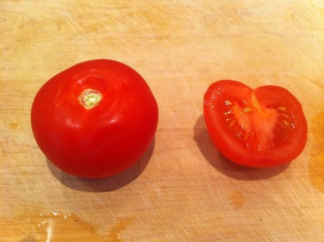 Cortar el tomate por la mitad, de arriba hacia abajo por lo que cortar a través whee el tallo era.