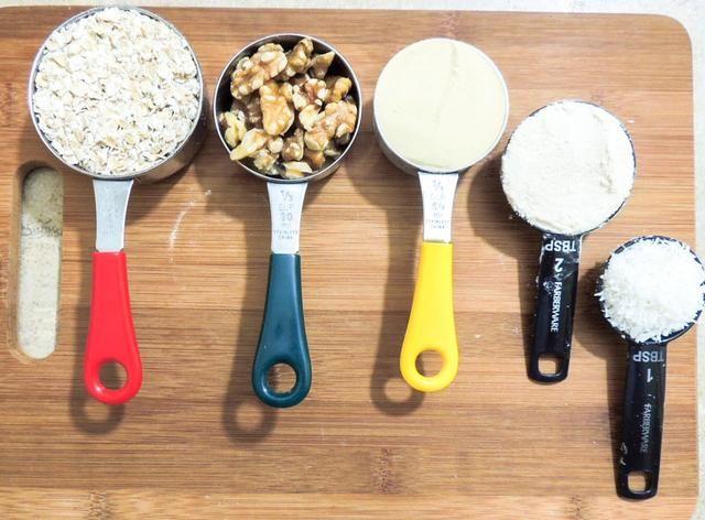 Mida los ingredientes secos. 1/2 taza de avena, 1/3 taza de nueces, 1/4 taza de proteína de guisante, 2 cucharadas de harina de coco.