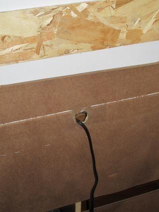 Utilice una herramienta dremel o pequeña sierra caladora para cortar un agujero para el cable eléctrico (o cable de enchufe múltiple) para pasar a través de la parte posterior del centro.