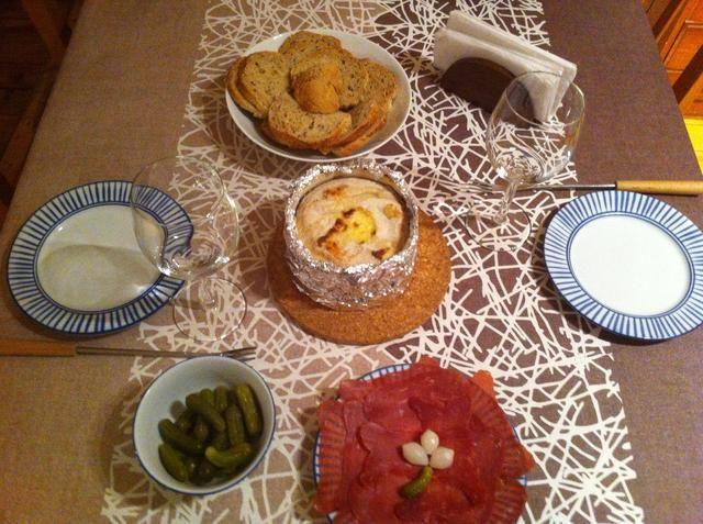 Servez le Fondue de Mont d'Or chaud à peine sorti du four, avec les tranches de viande sèche, les cornichons aigres et du pain