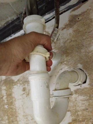 Aflojar el cierre de la conexión de la tubería de PVC recta (por encima de la trampa) a la tubería de metal (que entra en el fondo de la taza lavabo). Coge la pieza de PVC recta y deslícela hacia la tubería de metal ...