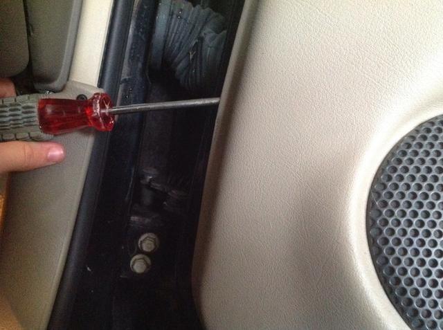 Ahora lo único que sujetan el panel de la puerta en pequeños clips que desconecta empujando el destornillador debajo del panel y tirando de él hacia afuera hacia usted.