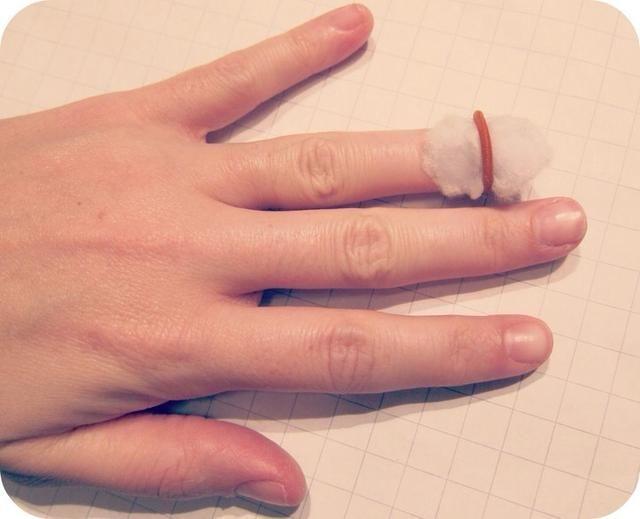 Paso 1: Remoje una pequeña bola de algodón en quitaesmalte, colóquelo directamente sobre el esmalte de uñas, luego deslice un pequeño pelo elástica alrededor para mantenerlo en su lugar.