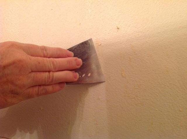 Utilice la espátula para raspar el papel húmedo fuera. Manténgase lo más a ras de la pared como sea posible, usted no quiere medir o cavar en la pared y hacer los agujeros.