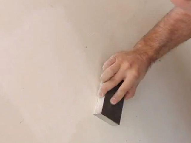 Después de que el compuesto para juntas es seco, suavizar el parche con el bloque de lijado hasta que la superficie es uniforme.