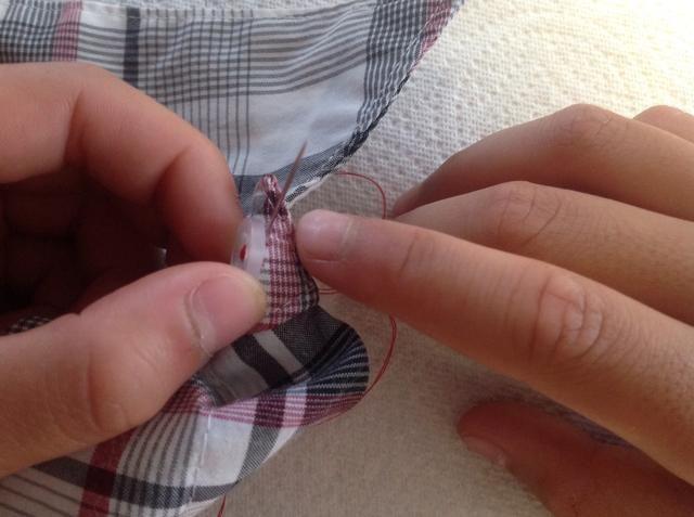 Para anclar la costura botón, llevar la aguja a través de la parte inferior del material SOLAMENTE. Asegúrese de no pasar por el ojal.