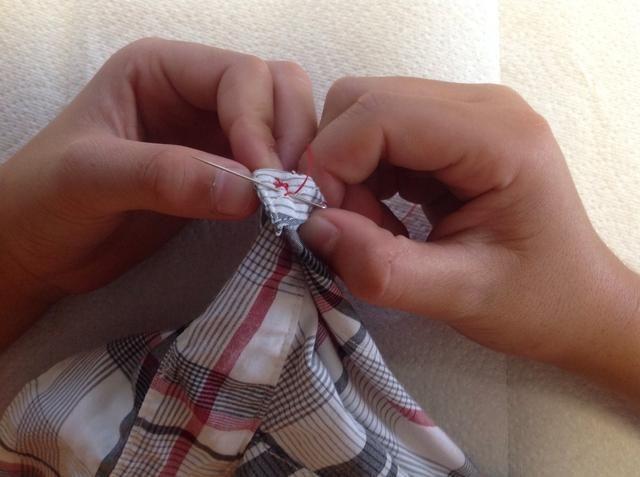A continuación, poner la aguja a través de un poco de la costura ya través del material.