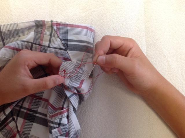 Tire de la aguja y el hilo un poco fuera del material y por debajo de la rosca para hacer un nudo. Tire con fuerza para hacer el nudo seguro.