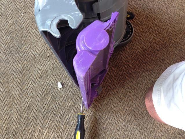 Con el destornillador de punta plana inserta entre los aullidos de plástico morado y el cuerpo gris del complemento vacío que carenado cabo haciendo palanca en ambos lados uniformemente