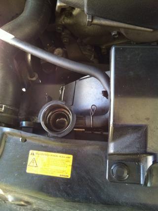 Retire la manguera que se fije entre el radiador y el depósito de líquido refrigerante.
