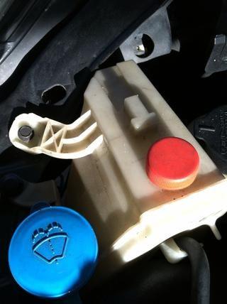 Retire el envase del líquido refrigerante del coche.