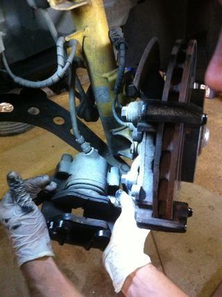 Sujetan la pinza de este modo y tire de la almohadilla interna paralela al pistón (hay resortes que lo mantienen unido al pistón).