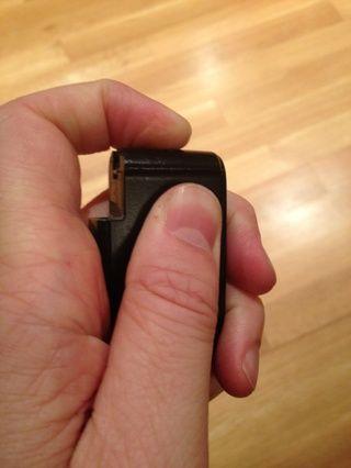Deslice suavemente la placa posterior hasta el fondo mientras se presiona en el mismo interruptor que utilizó para quitar la llave.