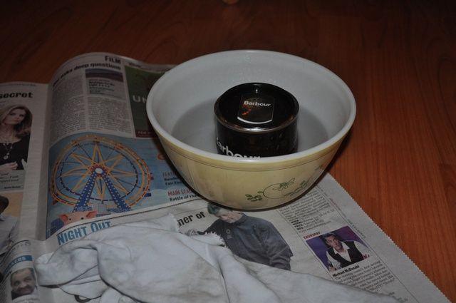 Calentar el agua en una tetera y verter en el recipiente. Coloque la lata de cera en agua caliente. Para ayudar a atrapar el calor y acelerar el derretimiento de la cera, ligeramente cubrirlo con la tapa.