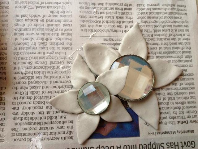 yo'm using the beads as the disc or eye (centre) of the flower. You can use any thing like funky buttons, beads, just anything which will make your frame look fab! Using the clay I made the petals.