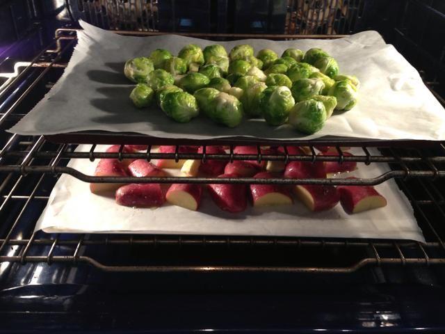 Coloque las dos bandejas en el horno frío. Patatas hasta las coles de Bruselas bajo. Las coles de Bruselas se cocinan más rápido. Aquí he cometido un error de la imagen, pero cambié up down mientras cocina. Ponga en el horno en 180C hornear