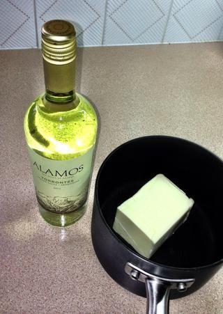 Derretir 3/4 libra de mantequilla sin sal, con una botella de vino blanco a fuego muy lento.