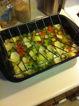 Agregue su caldo o agua (aproximadamente 2 pulgadas de profundidad) en la parte inferior de la bandeja para asar, agregue las verduras, y si usted tiene cualquiera de sobra frote hierba, se puede dispersar en el líquido.