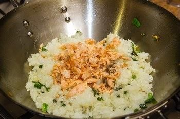 Cuando el arroz está recubierto con aceite, añadir el salmón desmenuzado y mezclar el wok de nuevo.