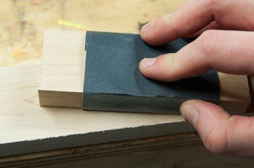 lijado manual con papel de lija envuelto alrededor trozo de madera