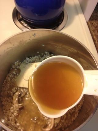 Agregue el caldo para cubrir 1/2 pulgada sobre el arroz, revuelva ocasionalmente.
