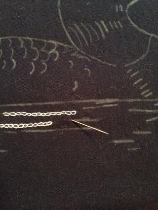 Estoy empezando una nueva línea de puntos de cadeneta. A partir de detrás de la tela de insertar la aguja y tire a través de la parte delantera.
