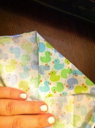 Después de pulsar se hace, crear las esquinas. Formando un triángulo, doblar una esquina abajo, los lados del revés juntos, alineando la línea hecha de prensado.