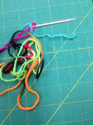 Enhebrar la aguja de plástico con un extremo de la pieza 2.5 yardas de hilo. Haga un nudo en el otro extremo.