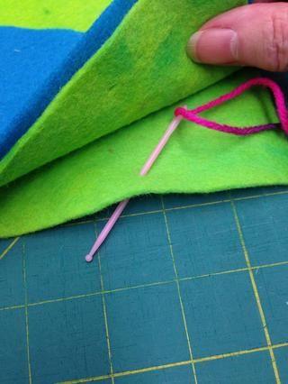 Inserte la aguja entre las secciones de la carrocería que van hacia la parte posterior para ocultar el nudo. Comience cerca de la mitad de la parte inferior del cuerpo.