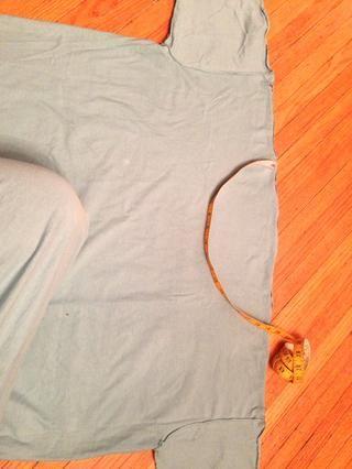 Utilice esta medida para esbozar una curva en el borde crudo de la T. mayor marca el principio, y la profundidad de la curva, asegurándose de que esté centrada entre las costuras de las mangas.