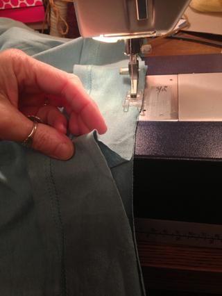 Ahora coser el dobladillo original de nuevo! Comience en un lado. Mantenga la tira dobladillo enseñado como vas por ahí con un tramo de costura recta. Usted quiere que se alimentan de manera uniforme, pero las curvas querrá estirarse.