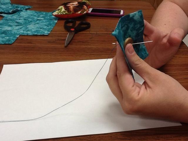 Siempre empezar desde la parte posterior del Botón de poner la aguja a través de la tela luego a través de un agujero del botón. Tire ajustado al nudo.