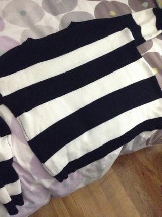 Comience poniendo su suéter sobre una superficie plana. Utilicé mi cama, pero una superficie dura probablemente funcione mejor.