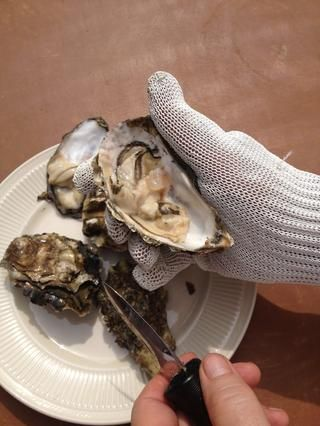Usa el cuchillo para raspar el exceso de ostras que se pega a la parte superior de la carcasa. Ejecute el cuchillo debajo de la parte inferior de la concha de ostra con la carne principal de ostras para aflojar para arriba.