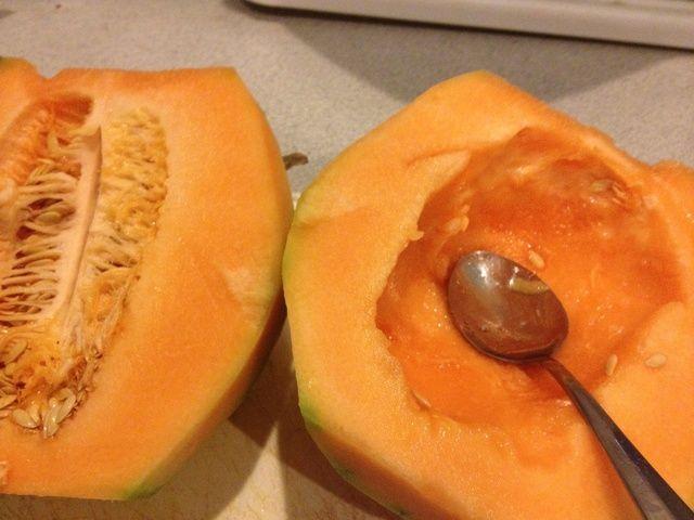 Con melón rebanada de pie en medio. Gut el interior utilizando una cuchara