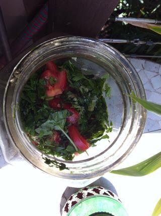 Picar los tomates maduros en cuartos y el reducir a la mitad otra vez y poner en el frasco. Añadir las hojas de albahaca en la parte superior de los tomates.