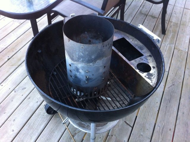 Dejar's get the fire going! Remove your top rack and place chimney starter in grill. Pack the bottom with 2 pages of newspaper.