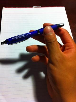 El agarre. Ligeramente sostenerlo entre el pulgar y el índice y el dedo medio. Sujete la pluma cerca de la punta (extremo más claro), como se ve en la foto.