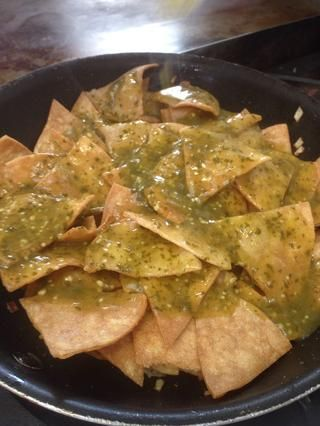 Añadir la salsa en ella. yo'm using my homemade tomatillo salsa. Coat all the tortilla chips with it.