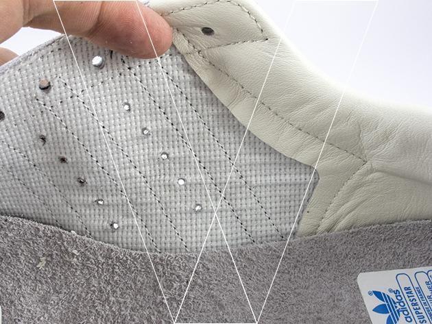 Desde el interior del zapato se puede ver cómo los agujeros perforados que corren entre las rayas laterales 3 se cortan limpiamente a través de la parte superior de cuero sin asperezas.