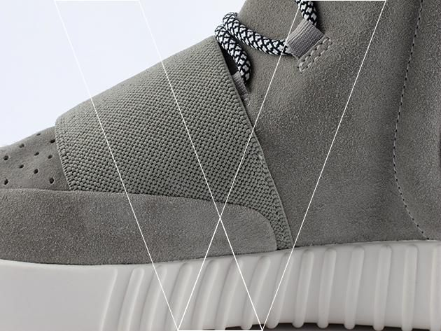 4. Correa de Ingreso: Yeezy Boost's have a midfoot strap for a locked down fit. Make sure that the strap folds under the suede toebox panel with a smooth join, showing no bump in the suede panel.