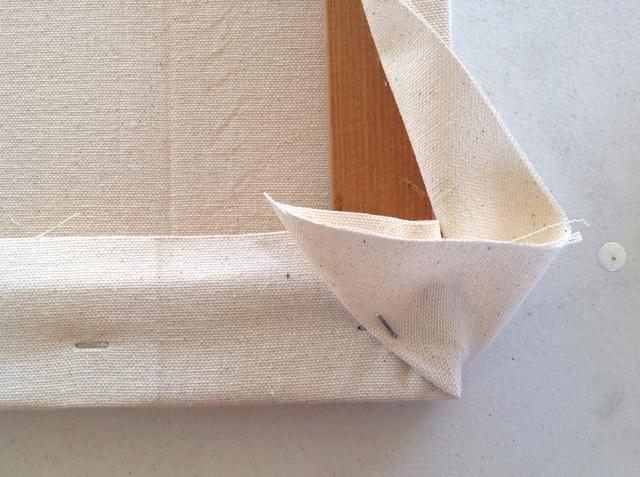 Esto es similar a envolver regalos. Tire de la pieza de esquina hacia el centro de la tela hasta que se hace un pliegue de la esquina del marco y de primera necesidad en su posición.