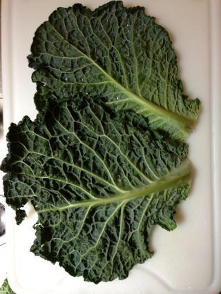 Tome el exterior de 2 hojas para cubrir el fondo de la olla. Añadir medio del ajo y unas hojas de menta