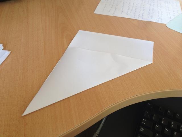 Doblar rápidamente un lado de la hoja para hacer una forma triangular con un extremo todavía rectangular, como se muestra en la foto.