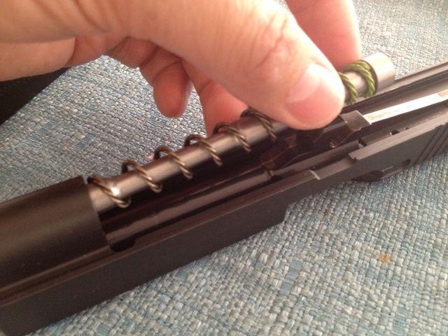 Empuje la guía del muelle recuperador un poco hacia adelante y ascensor desde la parte posterior para retirar el muelle recuperador y guía de la diapositiva.