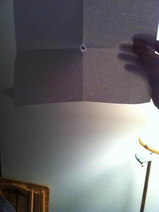 Mantenga la hoja de papel hasta con los brazos extendidos. Mantenga ambos ojos se abren a través de esta prueba. Y colocar el papel para que pueda ver un punto de enfoque en el agujero. En este caso el centro de un reloj.