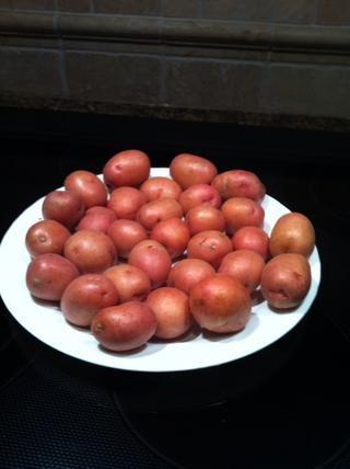 Organizar las patatas en un plato apto para microondas. Papas más grandes en el borde de la placa y los más pequeños en el centro.
