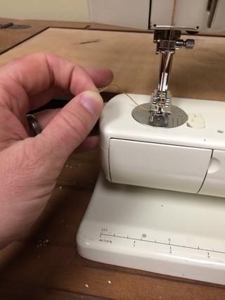 Coge el hilo superior con firmeza, pero no tire de ella. usted're going to lower the needle to grab the bottom thread, and you'll want to keep this thread end from disappearing.