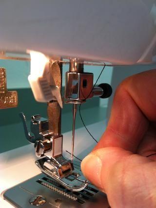 Coloque el hilo por el ojo de la aguja de adelante hacia atrás.