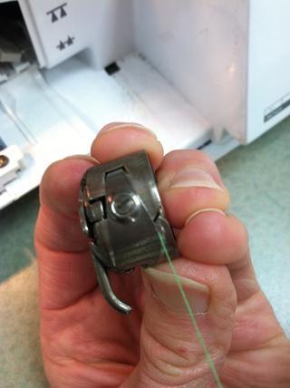 Deslice el hilo en la muesca que está cerca de la rosca de la bobina.